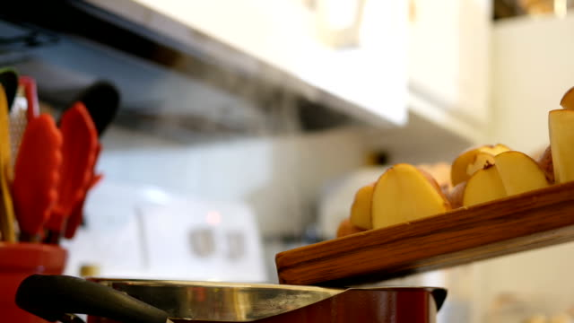 a woman drops some chopped potatoes into a boiling pot of water - молодой картофель стоковые видео и кадры b-roll