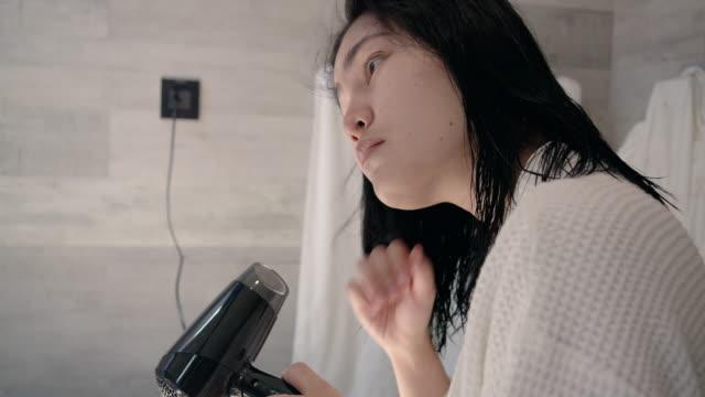 Woman drying hair in bathroom