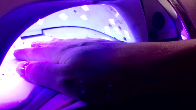 frau trocknet nagellack in einer uv-lampe in spa-salon. - maniküre stock-videos und b-roll-filmmaterial