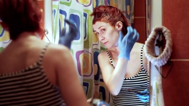 vídeos de stock e filmes b-roll de woman during self-isolation dyes her hair orange in the bathroom - covid hair