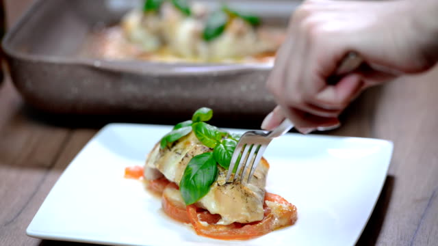 Woman eat delicious chicken fillet baked with caprese