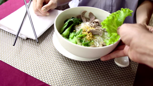 Woman eat traditional Vietnam Pho Bo (beef noodle soup) with chopsticks in restaurant. Waiter serve soup in cafe.