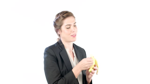 Woman eating a banana on a white studio background video