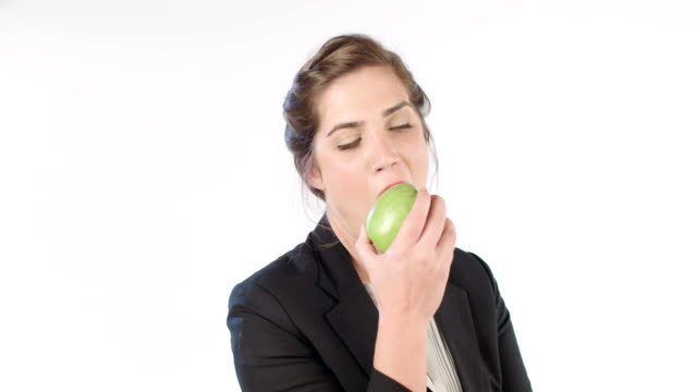 Woman eating a big green apple on a white studio background video