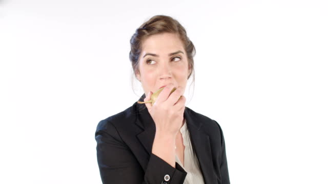 Woman eating a big pear on a white studio background video