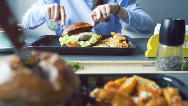 vídeos y material grabado en eventos de stock de mujer de comer una deliciosa hamburguesa con papas fritas. - cuchillo cubertería