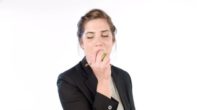 Woman eating a pear on a white studio background video