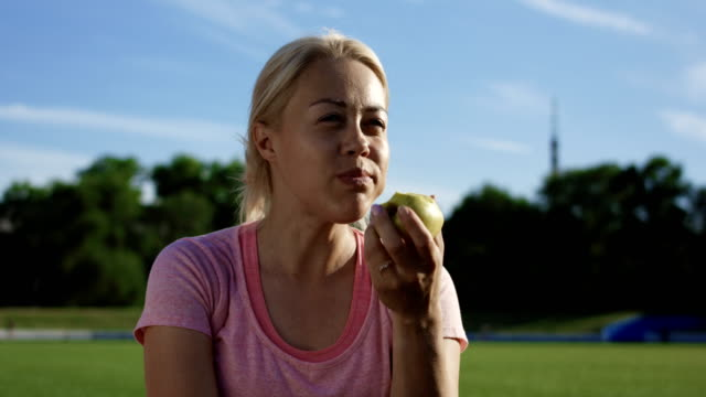 Woman eating apple in sunlight on field Sportive blond woman sitting on green athletic field in sunlight and enjoying apple snack stock videos & royalty-free footage