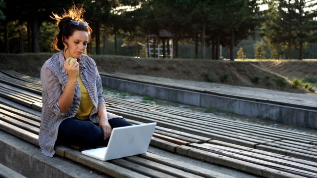 Woman eating apple while working video