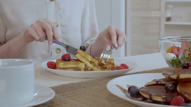 woman eating belgian waffles for breakfast - sciroppo video stock e b–roll
