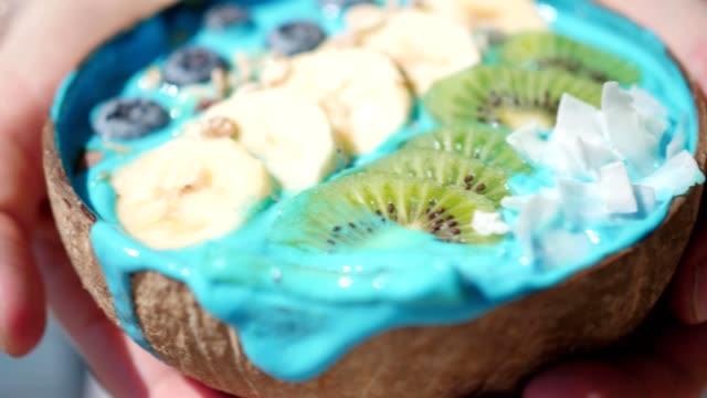 woman eating blue majik superfood smoothie from coconut bowl video