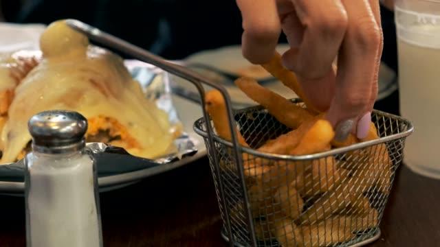 vídeos de stock, filmes e b-roll de mulher que come o hamburguer e fritadas francesas no restaurante 4k do diner - junk food