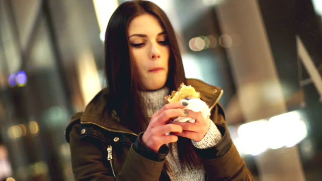 woman eating burger at the street - junk food stock videos and b-roll footage
