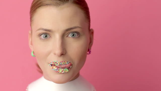 woman eating candies sticked on her lips video