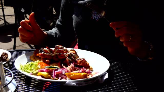 Woman eating chicken shish kebab video