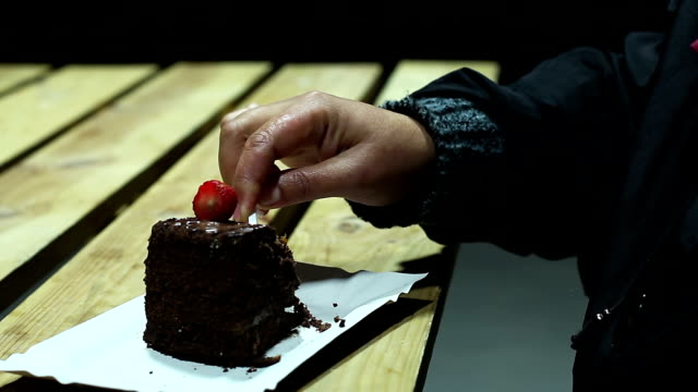 Woman eating chocolate cake at food festival, unhealthy addiction to video