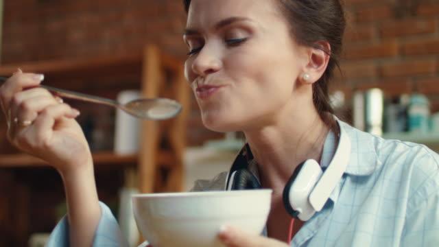 vídeos y material grabado en eventos de stock de mujer comiendo callosas con leche en la cocina. chica disfrutando de cereales para el desayuno - cuenco