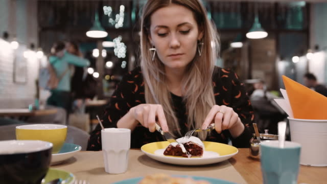 Woman eating dessert strudel at the restaurant using fork and knife. Slow motion video