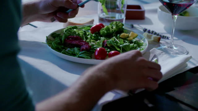Woman eating detail on dish.Four caucasian friends people mediterranean italian salad,meat steak and bread lunch or dinner. Summer party at home in modern house 4k handheld video