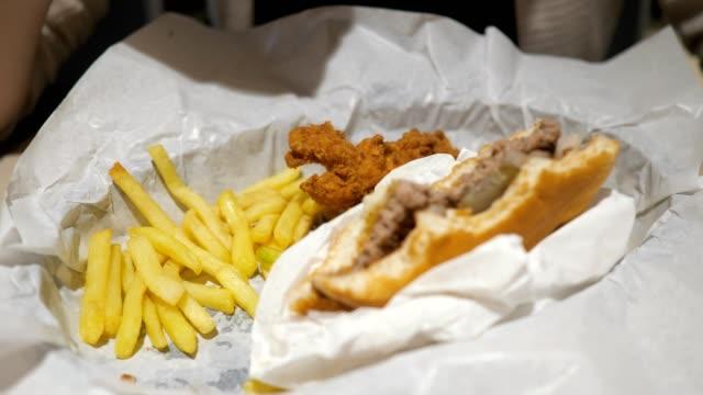 패스트 푸드 카페에서 감자 튀김, 닭고기와 햄버거를 먹는 여자, 음식 클로즈업. - burger and chicken 스톡 비디오 및 b-롤 화면