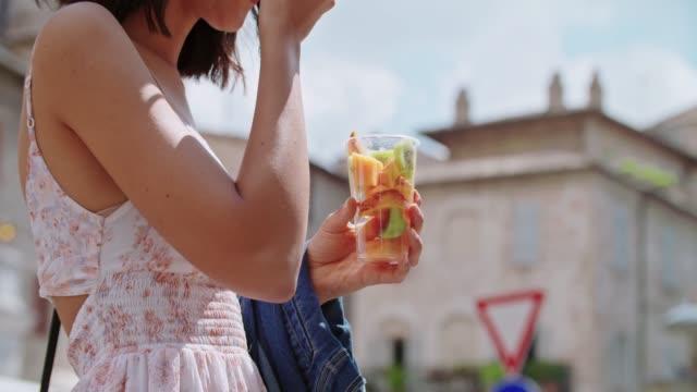 vídeos de stock, filmes e b-roll de mulher comendo salada de frutas na cidade ou cidade velha. turista tem uma pausa comendo uma salada de frutas em dia ensolarado. detalhe de mulher colhendo com garfo uma salada de frutas - fruit salad