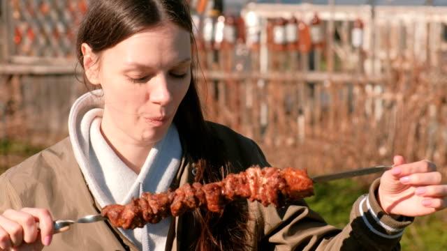 晴れた日の春の裏庭に串に刺して、熱い肉のシャシリク バーベキューを食べる女。 ビデオ