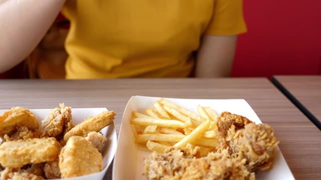 vídeos de stock, filmes e b-roll de mulher comer junk food frango, câmera lenta - alimentação não saudável