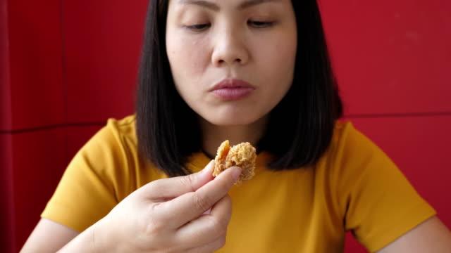 정크 푸드를 먹는 여자 - burger and chicken 스톡 비디오 및 b-롤 화면