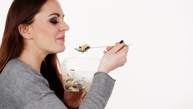 Woman eating oatmeal with fruits 4K video