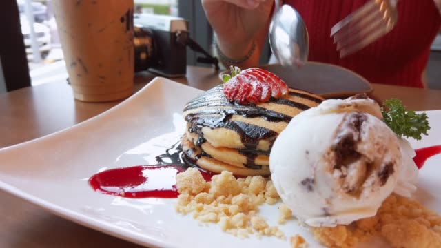 Woman eating pancake with chocolate sauce and ice cream.