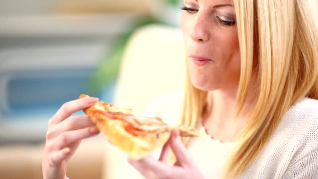 Woman eating pizza. video