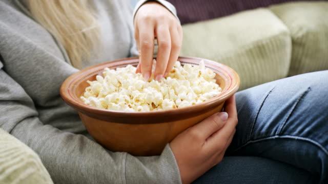stockvideo's en b-roll-footage met vrouw eten popcorn zittend op de sofa in de woonkamer - popcorn