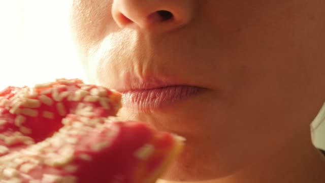 woman eating red, pink donut, doughnut, macro, close - obsoleto video stock e b–roll