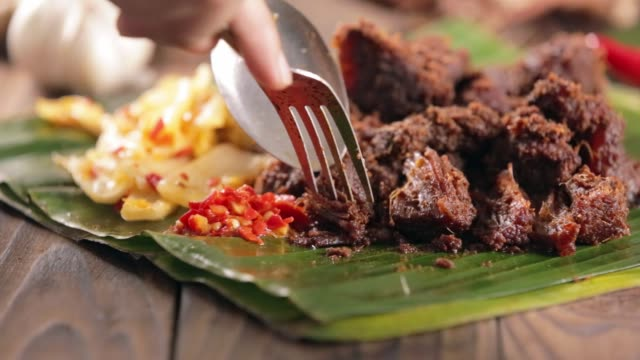 Woman eating rendang jerky beef stew with mustard leave and sambal Woman eating rendang jerky beef stew with mustard leave and sambal jerky stock videos & royalty-free footage
