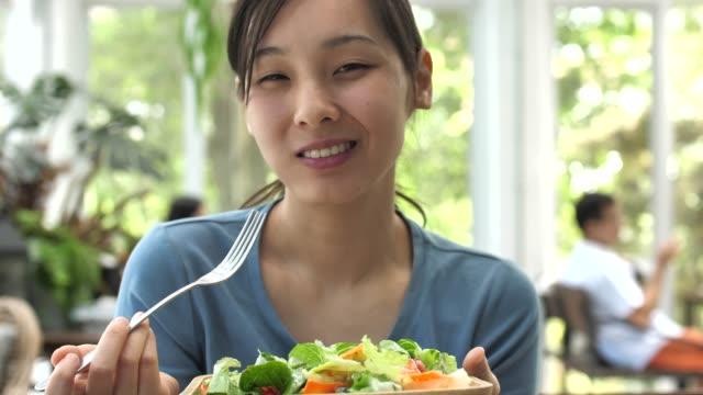 女性は、カメラを見て、サラダと笑顔を食べる - サラダ点の映像素材/bロール