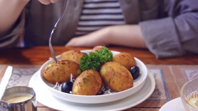 vídeos de stock e filmes b-roll de woman eating salt cod food, pasteis de bacalhau,  bacalao in macau restaurant - bacalhau