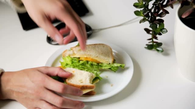 vídeos de stock, filmes e b-roll de mulher comendo sanduíche enquanto trabalhava. sanduíche de brinde fresco com queijo e salada no local de trabalho. almoço de trabalho - almoço