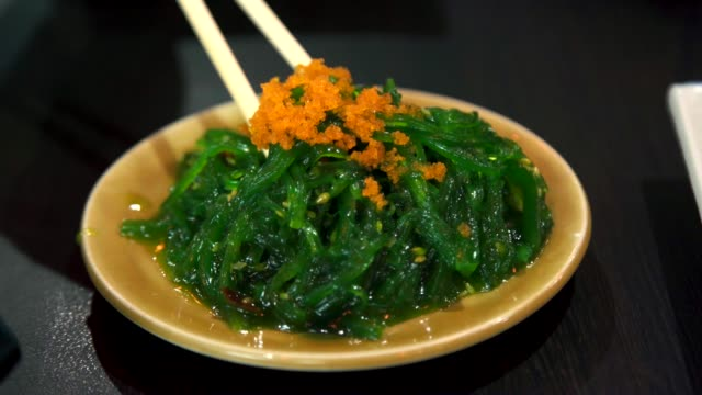 Woman Eating Seaweed Salad with Shrimp Eggs in Japanese Food. Woman Eating Seaweed Salad with Shrimp Eggs in Japanese Food. kelp stock videos & royalty-free footage