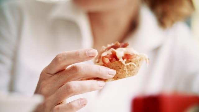 vídeos de stock e filmes b-roll de woman eating snack in restaurant - sanduíche