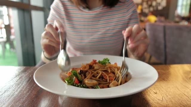 donna che mangia spaghetti al ristorante. - cucina italiana video stock e b–roll