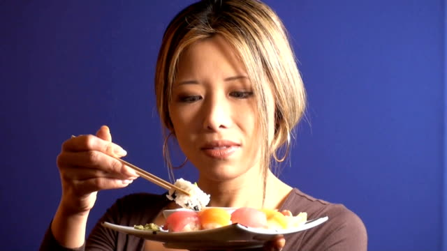 Woman eating sushi from plate - HD 1080p video