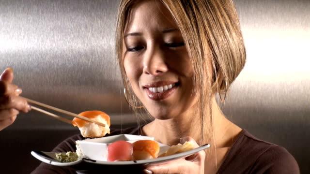 寿司を食べる女性のステンレス鋼のバックグラウンド。 ビデオ