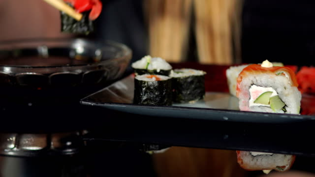 Woman eating sushi with chopsticks on black table. video