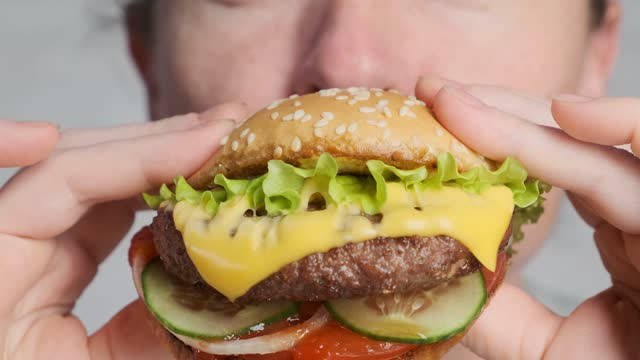 Woman eating tasty beef burger with cheese and golden bun closeup. Woman eating tasty beef burger with cheese and golden bun closeup. fat nutrient stock videos & royalty-free footage