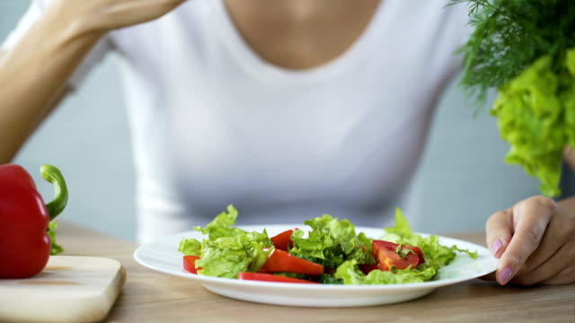 Woman eating vegetable salad, observing diet and counting calories, wellness video