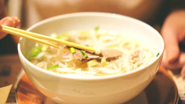Woman eating Vietnamese classic noodle soup.