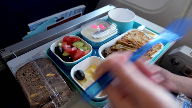 Woman eats in airplane during flight food served on a tray, hand closeup. Lunch in plane: bread, meat with vegetables and rice, pieces of cheese, dried apricot, salad and beverage in cup. Woman is eating in airplane during flight food served on tray, hand with fork closeup. tray stock videos & royalty-free footage