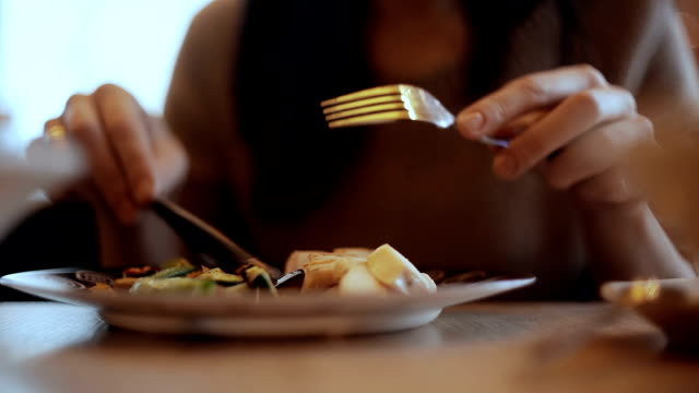 Woman eats vegetable and meat in cafe video