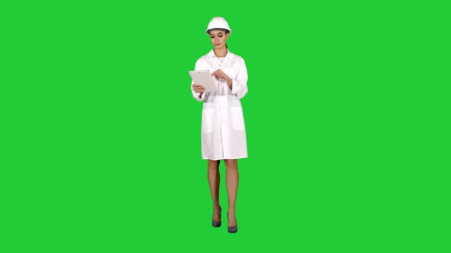 Woman engineer checking information and objects on her tablet on a Green Screen, Chroma Key