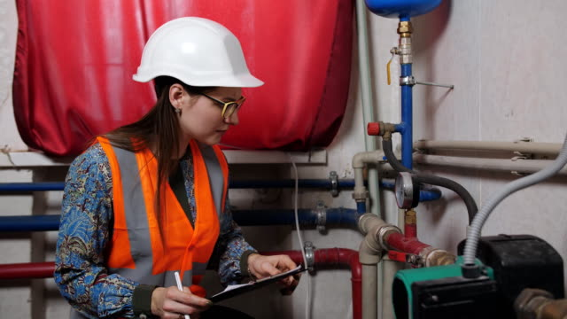 woman engineer checks the meter readings in the boiler room. - basement stock videos & royalty-free footage